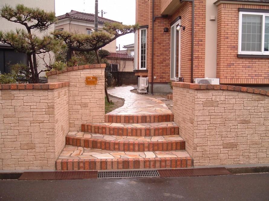 落ち着いた雰囲気のスタンプウォールが引き立てるアプローチ 新潟市M様邸