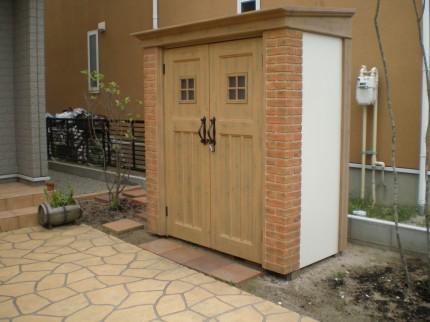 玄関前にお洒落なディーズガーデンの物置・カンナと門壁で玄関前をリフォーム